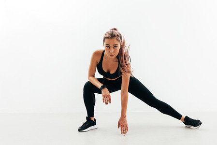 Young healthy woman stretching her body during fitness training