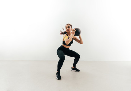 Muscular woman doing sit ups with medicine ball indoors