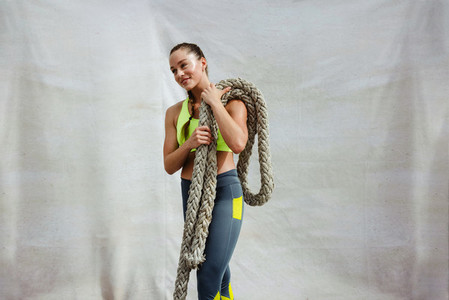 Female athlete with battle rope on white background