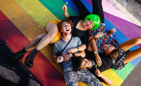 Four young queer people lying down together