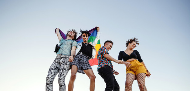 Cheerful group of queer individuals dancing at pride