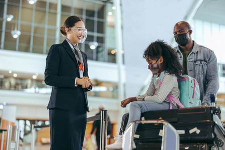 Airport staff at boarding gate assisting tourist family