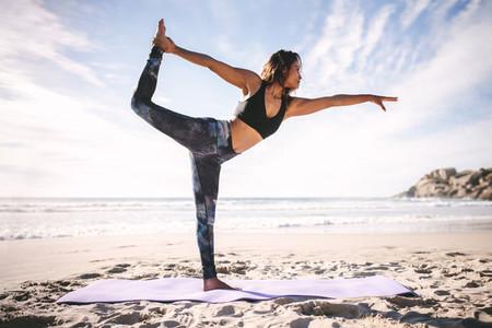 Woman doing Natarajasana yoga pose on beach