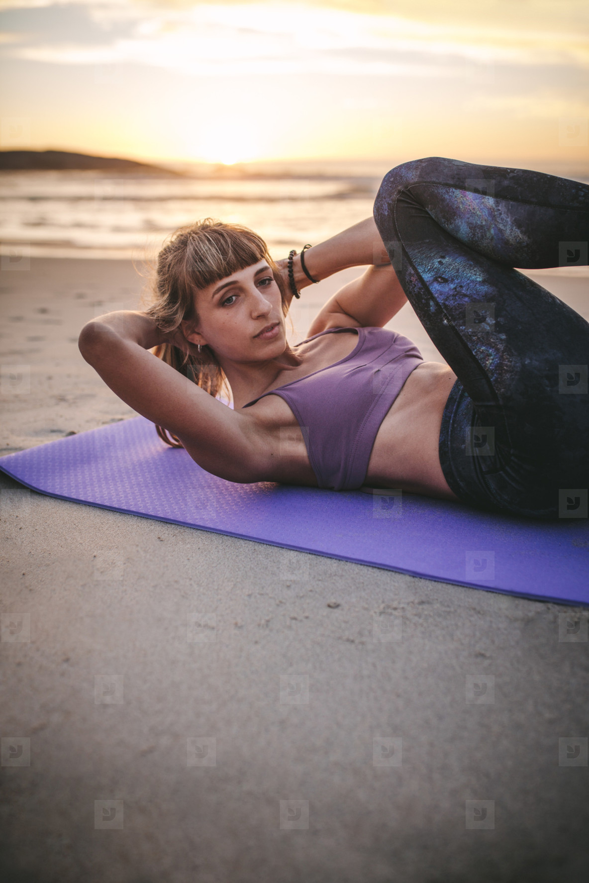 Fit woman doing situps at beach