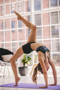 Woman doing yoga stretches at fitness studio