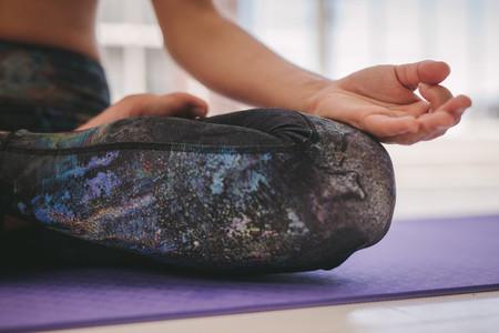 Woman meditating in Padmasana yoga pose at class