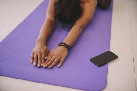 Woman doing stretching workout on exercise mat
