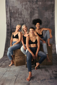 Full length shot of diverse women laughing together in a studio