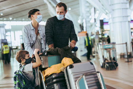 Family of three walking at airport in pandemic