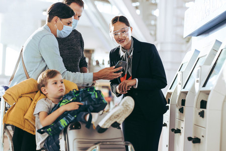 Ground staff assisting family at airport
