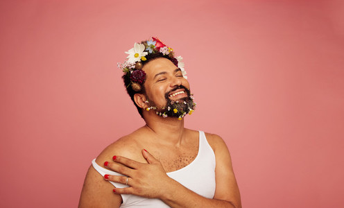 Smiling gay person wearing flowers on bed and beard