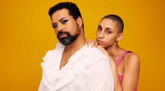 Drag queen with androgynous woman on yellow background