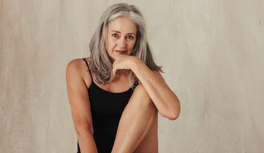 Grey haired woman feeling confident in her natural body