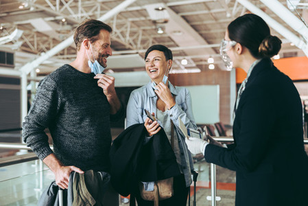 Attendant assisting couple at airport check in counter