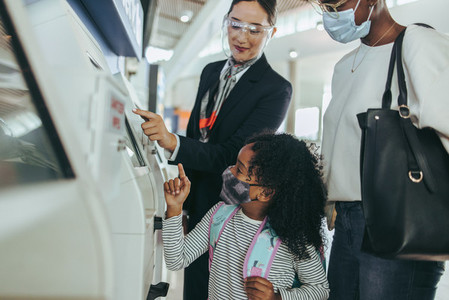 Attendant helping a family doing the self check in at the airpor