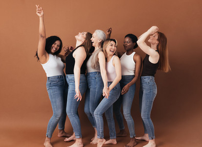 Six diverse women laughing together  Females with different body types having fun while standing against a brown background
