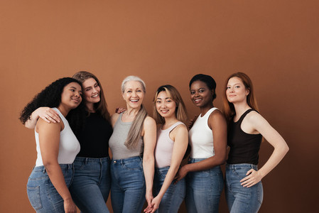 Multi ethnic group of women of different ages posing against brown background looking at camera