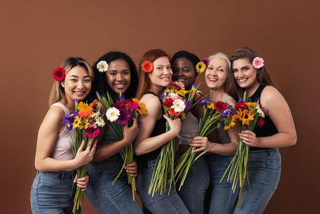Six smiling women of different ages looking at camera in a studio  Happy diverse females with bouquets and flowers in their hairs standing together