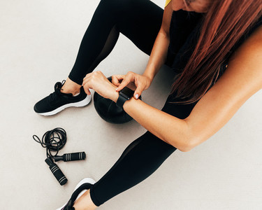 Shot of young woman sitting outdoors with skipping rope and medicine ball looking at smartwatch after training