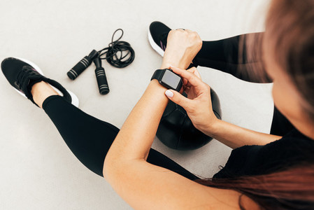 Cropped shot of unrecognizable sportswoman looking at smartwatch outdoors