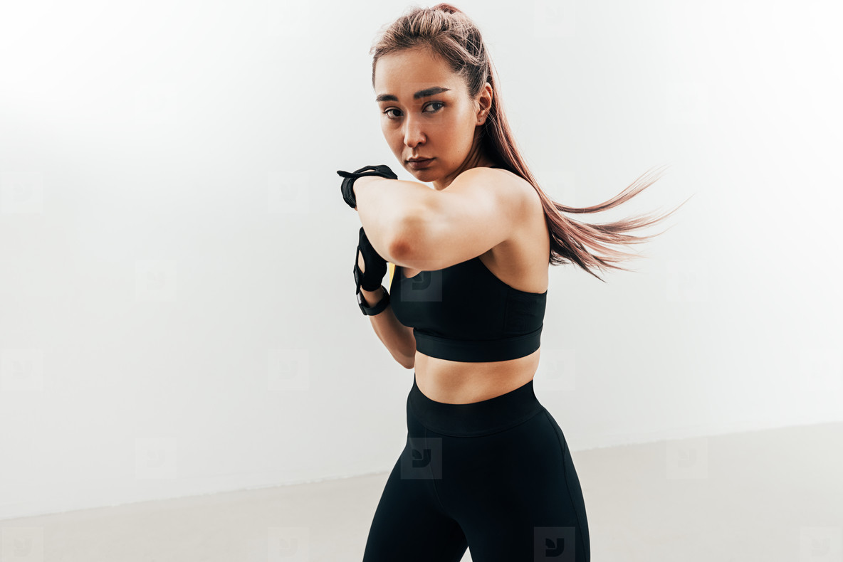 Woman doing kickboxing workout against a white wall  Female practicing punches