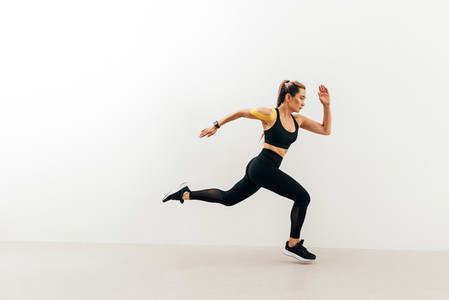 Side view of female athlete sprinting near a white wall