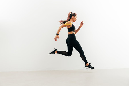 Runner in sport clothes sprinting near a white wall  Woman with kinesiology tape on shoulder jogging indoors