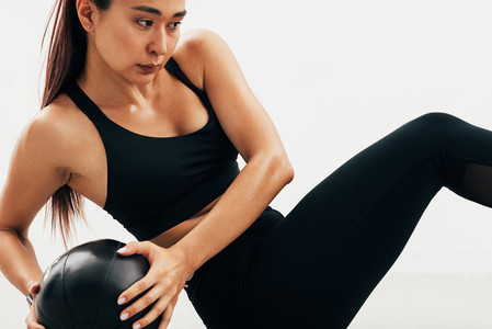 Close up of young Asian woman exercising with medicine ball indoors