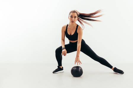 Young fit woman in sports clothes doing warming up exercises with a medicine ball