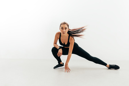 Asian woman warming up before workout against white wall
