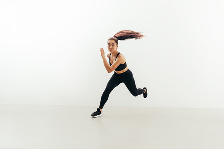 Front view of muscular woman running in studio against white wall