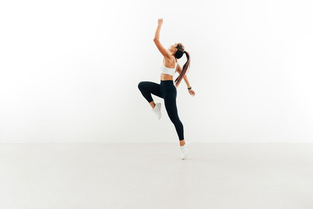Side view of young female athlete jumping in the air raising hand up against white wall