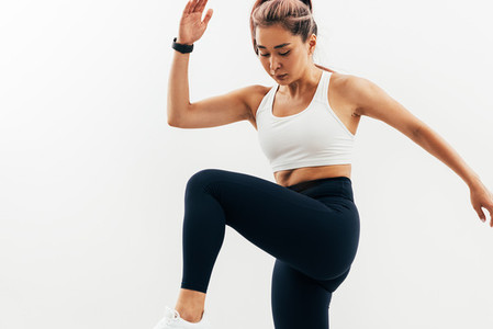 Young Asian woman doing warming up exercises against white wall