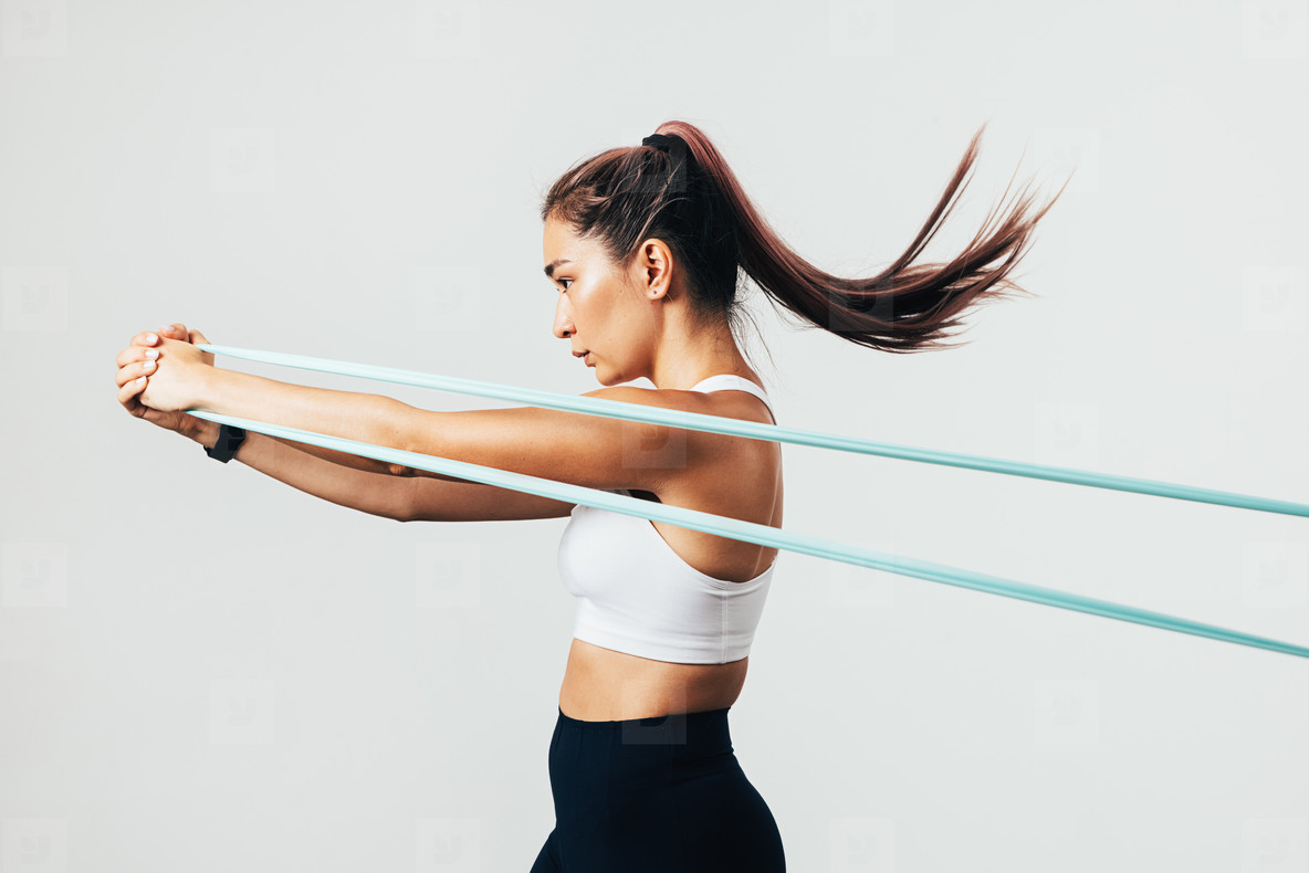 Side view of sportswoman exercising with resistance band against white wall