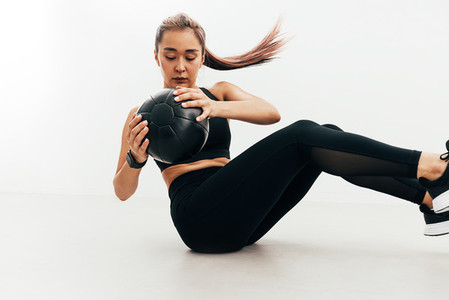 Woman doing abdomen exercises sitting indoors holding a medicine ball