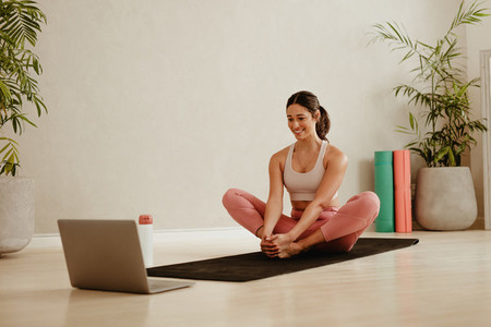 Woman doing exercises at home watching online training