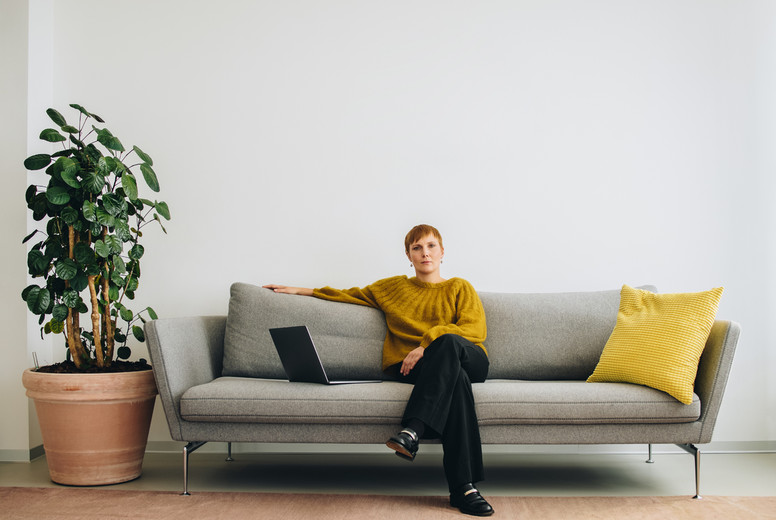 Female executive sitting on sofa in office lobby