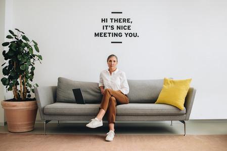 Female business professional sitting on sofa