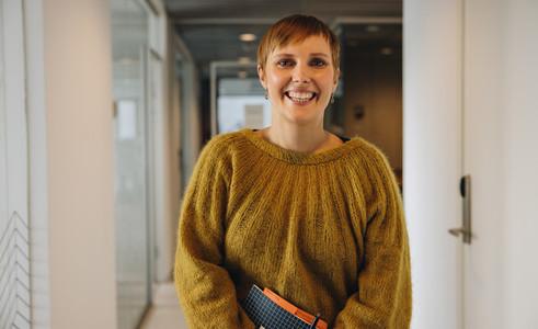 Positive businesswoman at office corridor