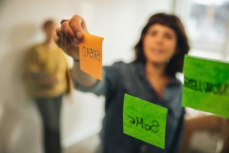 Woman brainstorming using adhesive notes in meeting