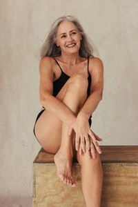 Cheerful mature woman posing in her natural body