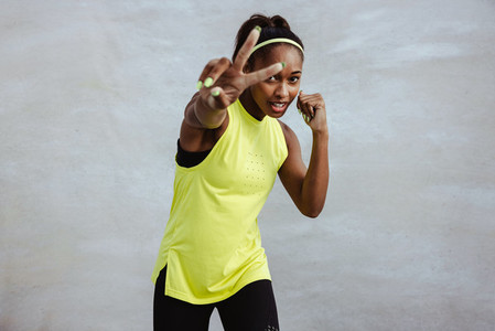 African sportswoman exercising with peace handsign