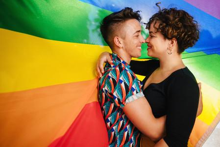 Romantic queer couple bonding against a rainbow flag