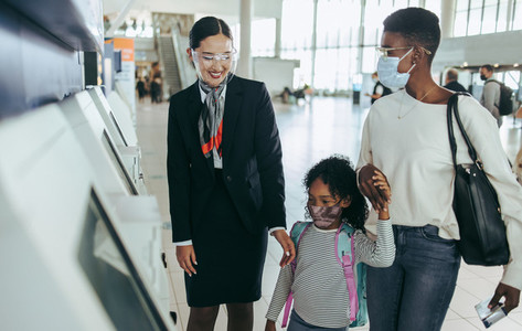 Family at airport with airlines staff during pandemic
