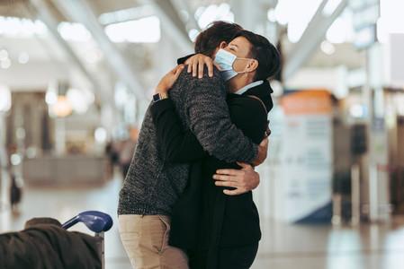 Woman welcoming man at airport post pandemic