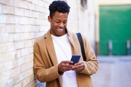 Young black man typing on his smartphone leaning against a brick wall in the street
