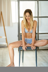 Caucasian girl in blue lingerie sitting on a chair at home