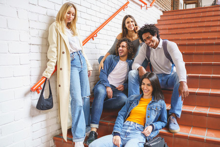 Group of students with ethnic variety  sitting on some street steps having fun together