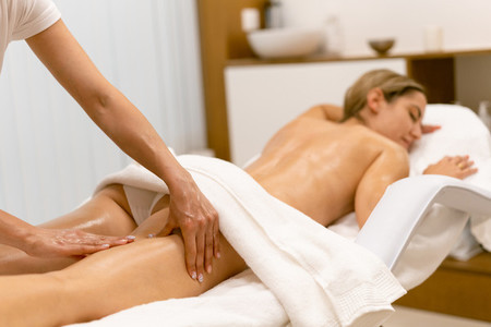 Beauty salon professional pouring oil from a massage candle on the back of his patient