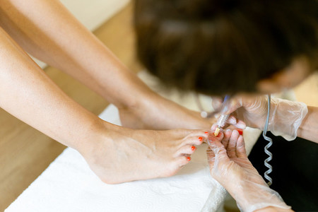 Beautician giving a pedicure painting her clients nails in a beauty centre